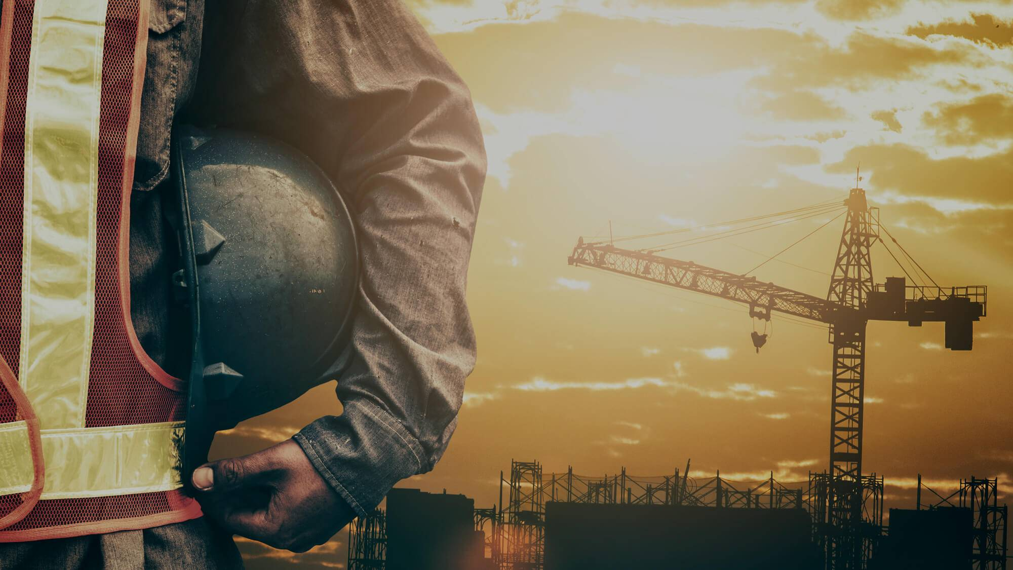 A picture of a man holding a hard hat on his side with a large crane in the background.